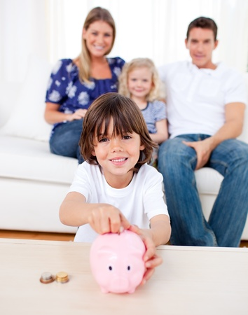 Cheerful little boy inserting coin in a piggybank photo