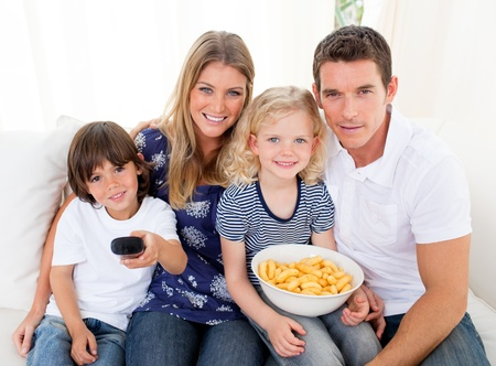 Loving family watching television sitting on sofa photo