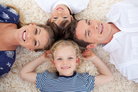 Smiling young family lying on the floor Stock Photo - 10250505