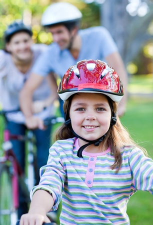 Smiling little girl riding a bike photo