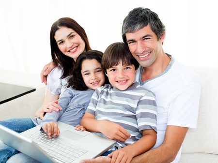 personal computers: Happy family using a laptop sitting on sofa