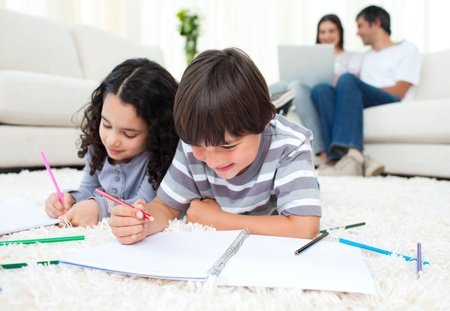 children writing: Adorable children drawing lying on the floor  Stock Photo
