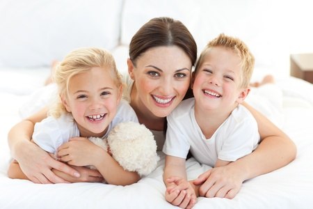 Happy mother and her children lying on a bed photo