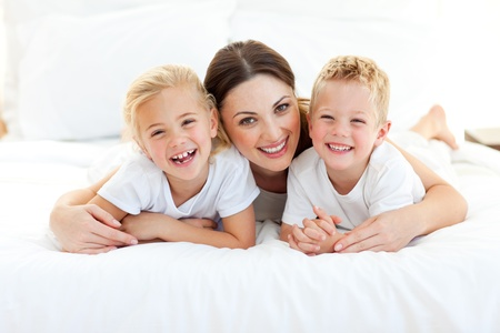 madre e hijo: Riendo a niños jugando con su madre acostado en una cama Foto de archivo