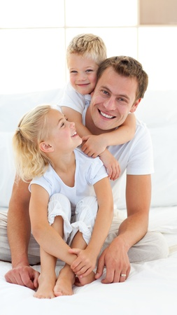 father with child: Caring father with his children sitting on bed