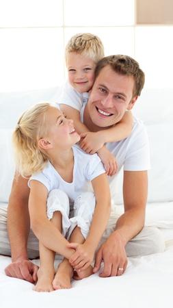 pere et fille: P�re attentionn� avec ses enfants assis sur lit  Banque d'images