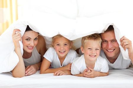familia jugando: Familia joven jugando juntos en una cama  Foto de archivo