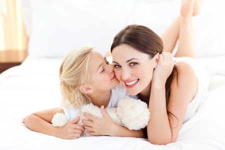 mother and daughter: Cute little girl kissing her mother