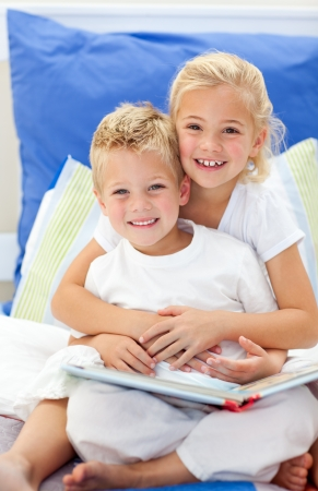 gleeful: Blond brother and daughter reading books Stock Photo