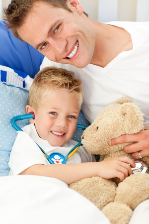 Handsome father and his sick son playing with a stethoscope Stock Photo - 10249852
