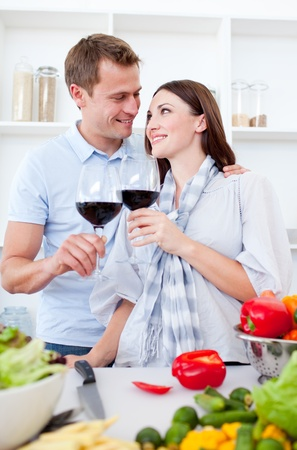 Affectionate couple drinking wine while cooking photo