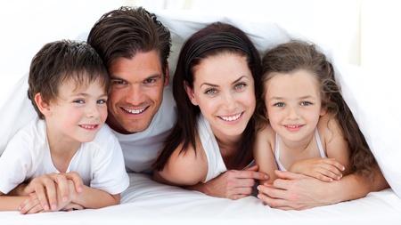 familia abrazo: Retrato de una familia sonriente, acostado en cama