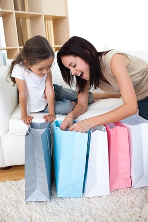 Happy Mother and daughter unpacking shopping bags photo