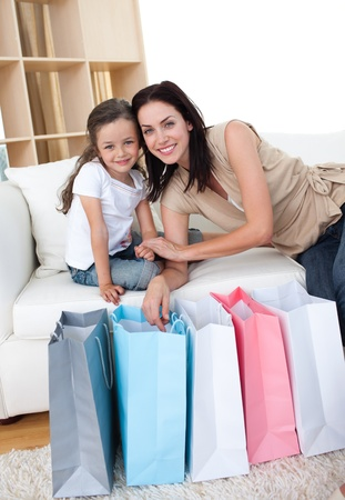 Smiling mother and her daughter opening shopping bags photo