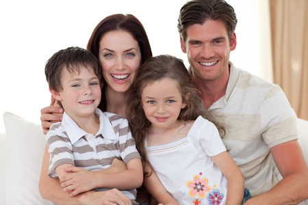 cuddling: Portrait of a smiling family on the sofa Stock Photo