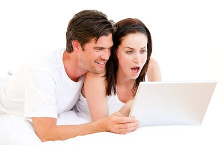 Surprised couple using a computer lying on their bed photo