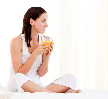 Cheerful woman drinking an orange juice sitting on her bed photo