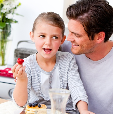 growing together: Smiling father and his daughter having breakfast together
