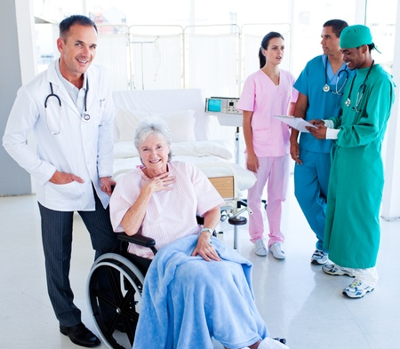 Positive medical team taking care of a senior woman photo