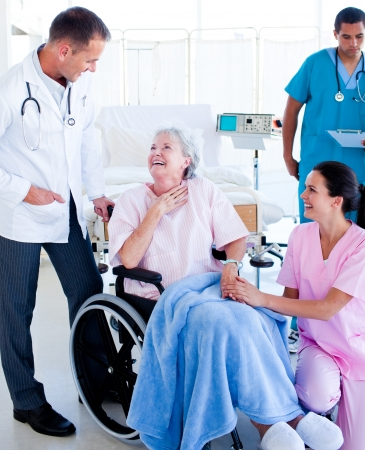 Confident medical team taking care of a senior woman photo