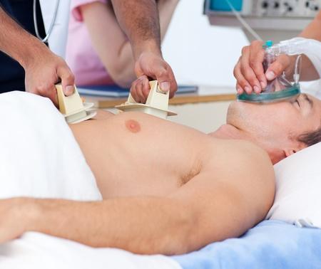 defibrillator: Close-up of a medical team resuscitating a patient