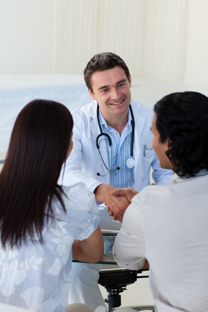 Smiling doctor explaining diagnosis to a couple photo