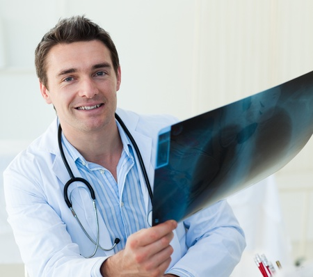 Attractive doctor examining an x-ray Stock Photo - 10247201
