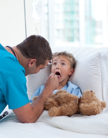 Male doctor examining child throat photo