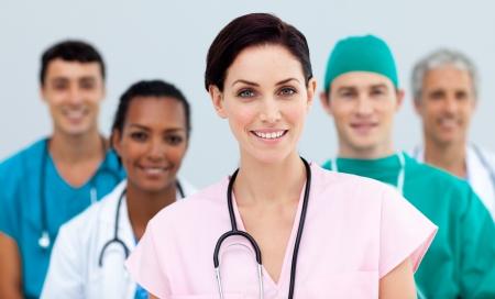 grupo de doctores: Hembra m�dico permanente en frente de su equipo Foto de archivo