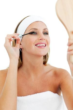 Smiling woman putting mascara photo