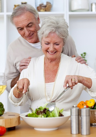 Happy senior couple eeating a salad in the kitchen photo