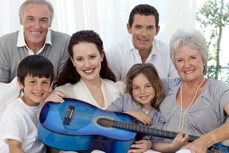 Portrait der Familie mit einer Gitarre im Wohnzimmer Standard-Bild