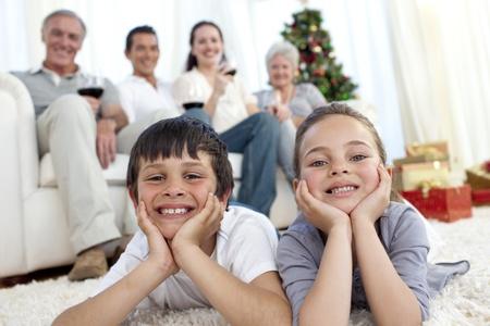 winter party: Fratello e sorella sul pavimento con la loro famiglia a Natale Archivio Fotografico
