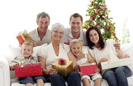 holding a christmas ornament: Family holding Christmas presents at home