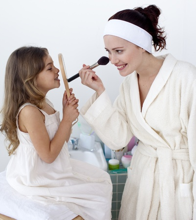 mother with daughter: Madre aplicar colorete con su hija