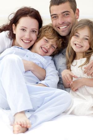 pijama: Retrato de familia joven tumbado en la cama Foto de archivo