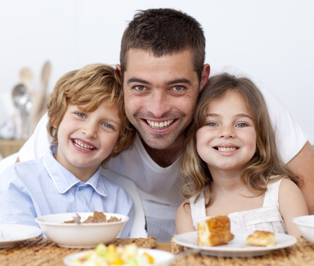 Portrait of children having breakfast with their father photo
