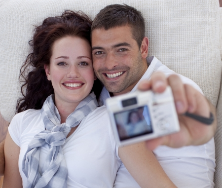 Portrait of couple playing with digital camera photo