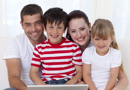 Smiling family at home using a laptop photo