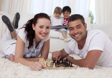 Happy couple playing chess on floor in living-room photo