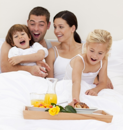 Family having breakfast in bed in the morning photo