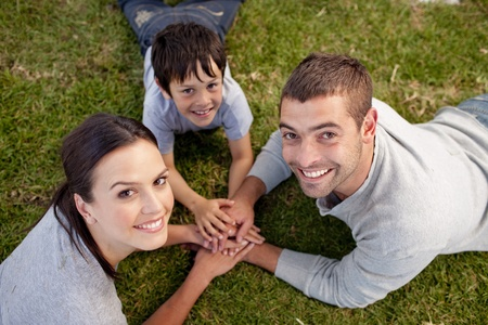 Parents and kid lying on garden with hands together photo