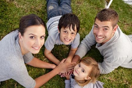 ensemble mains: jeunes Parents et kid gisant sur jardin avec les mains ensemble