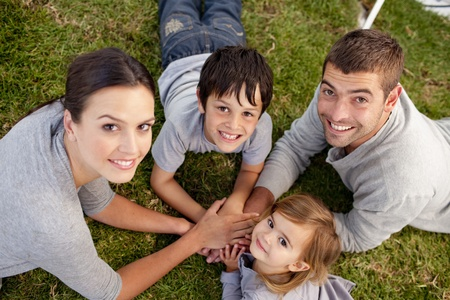 young Parents and kid lying on garden with hands together photo