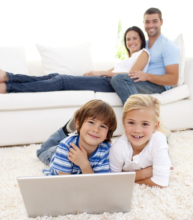 Children playing with a laptop and parents lying on sofa photo