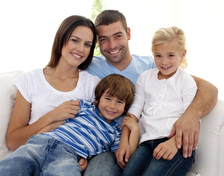 Smiling young family sitting on sofa photo