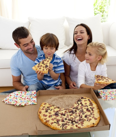 familia comiendo: Padres e hijos comer pizza en Salón Foto de archivo