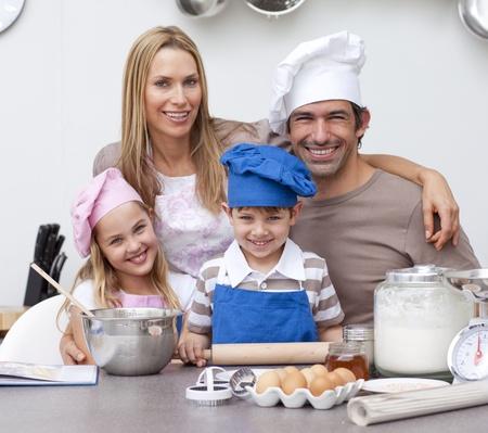 Lachende ouders het helpen van kinderen bakken in de keuken