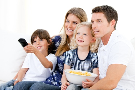 changing channels: Smiling family watching a film at television Stock Photo