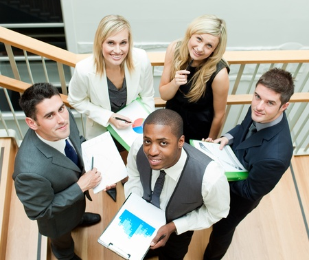 Business team working on stairs and smiling at the camera Stock Photo - 10247308